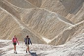 Couples hiking in mountains, Death Valley, California, USA