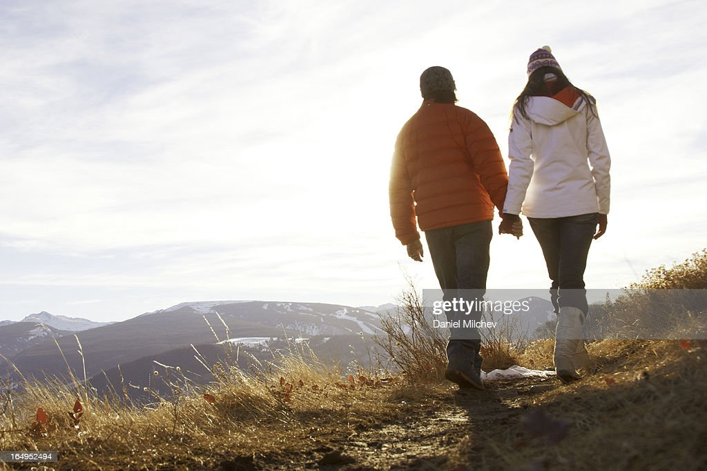 Couples holding hands, while waling on a trail. : Stock Photo