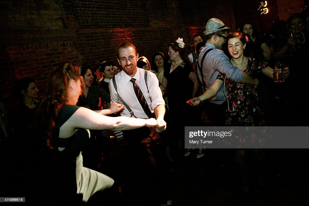 Couples in 1940s costumes dance to swing band 'The Red Roosters' at The Blitz Party on February 22, 2014 in London, England. Deep in an East End bunker hundreds of vintage enthusiasts partied like it was 1940 in a range of wartime costumes. They danced to Swing and Jazz music while drinking themed cocktails, as they embraced the glamour of and nostalgia for the era.
