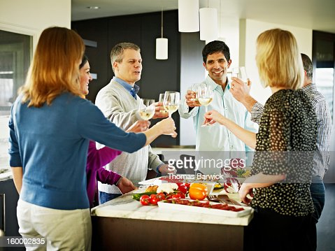 couples in home kitchen toasting wine glasses : Stockfoto