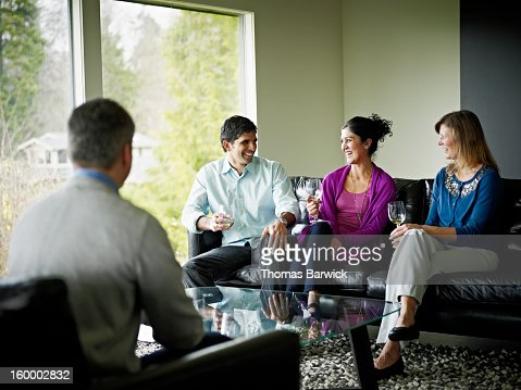 Couples in living room drinking wine and laughing : Stock Photo