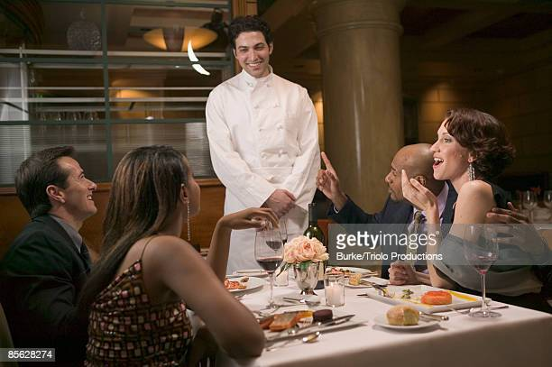 Couples in restaurant talking to chef