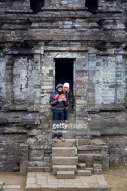 Couples inspect their digital camera after pose at a Temple in Complex Temple at Dieng Dieng plateau in Central Java is part of the district of...