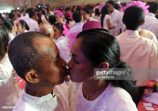 Couples kiss during a free mass wedding in Manila of February 14 2014 Some 900 Couples exchanged vows inside a packed Clam shell tent on Valentine's...