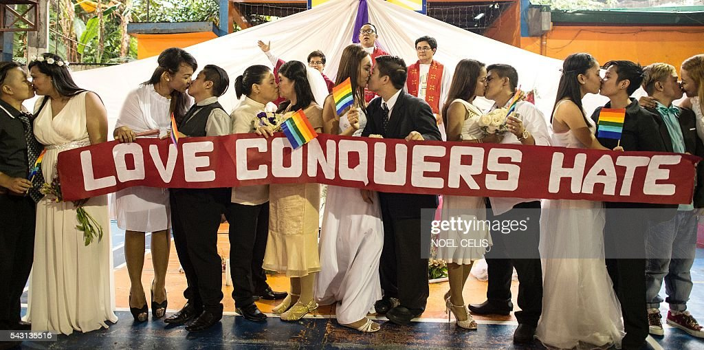 Couples kiss together as members of the lesbian, gay, bisexual and transgender (LGBT) community take part in a 'Rite of Holy Union' ceremony in Manila on June 26, 2016, that coincided with Gay Pride celebrations the day before. The Philippines has a vibrant gay scene despite a macho culture and opposition from the Roman Catholic Church, but there are no anti-discrimination laws in the country and same-sex relationships are not officially recognised. / AFP / NOEL