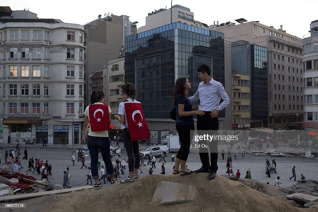 Couples look out atop a halted construction site in Gezi Park in Istanbul Turkey on June 6 2013 Refusing to yield to a week of protests in dozens of...