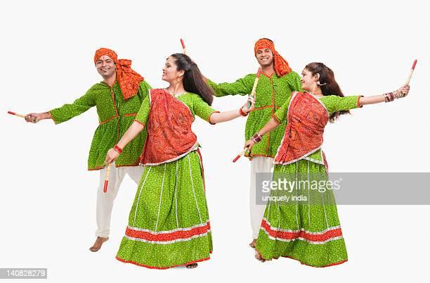 Couples performing dandiya