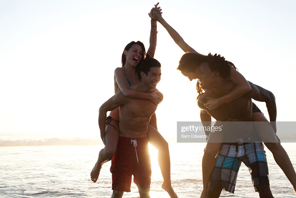 Couples playing in waves on beach : Stock Photo