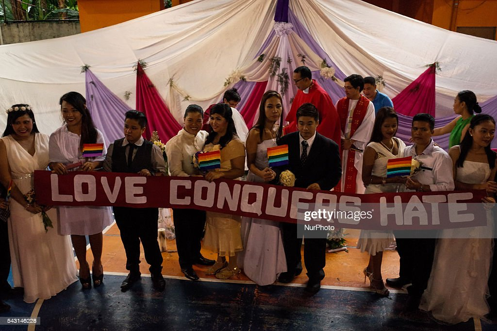 "LGBT couples pose for photographers during a mass wedding ceremony at Barangay Sangandaan in Quezon City on Sunday, 26 June 2016. The LGBT Christian Church, a small Christian ecumenical group, performed its own ""wedding rites"" for eight couples at a basketball court on Sunday, although same-sex unions are not legally recognized and rejected by the dominant Roman Catholic church in the country."