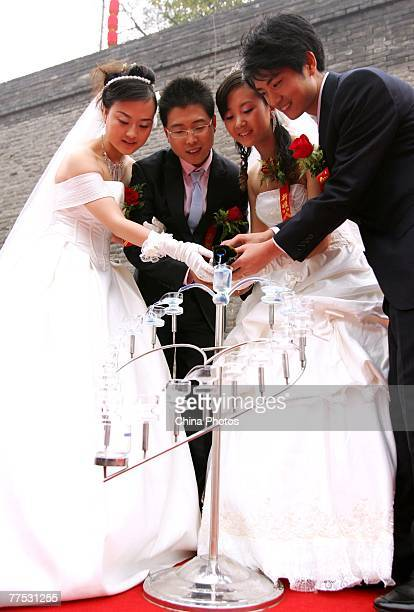 Couples pour champagne during a group wedding ceremony at the Xian City Wall on October 27 2007 in Xian of Shaanxi Province China 16 couples from a...