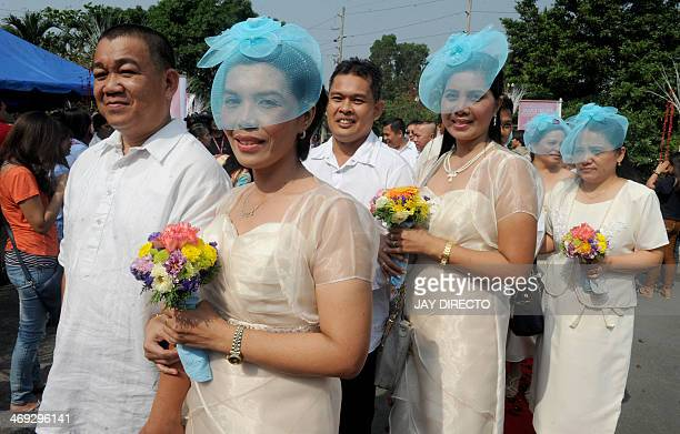 Couples queue for a free mass wedding in Manila of February 14 2014 Some 900 Couples exchanged vows inside a packed Clam shell tent on Valentine's...