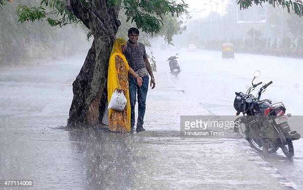 A couples seeks shelter under a tree during a heavy rain on June 14 2015 in Jaipur India The city sizzling as heat wavelike conditions prevailed...