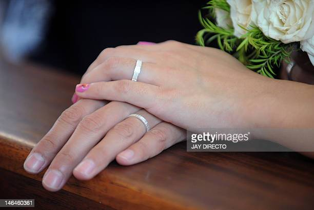 A couples shows their wedding ring during a mass wedding at a University chapel in Manila on June 17 2012 Church weddings are an important part of...