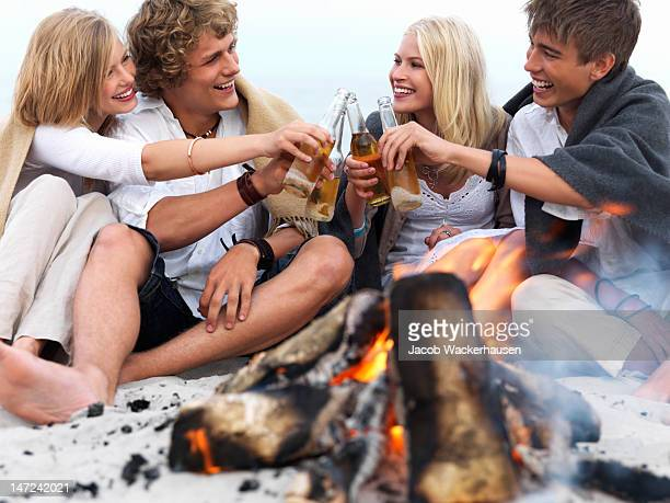 Couples sitting by a fire on the beach with beer