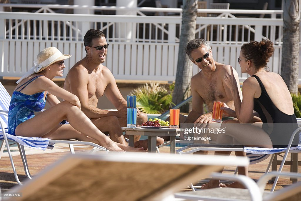 Couples sitting by pool : Stock Photo