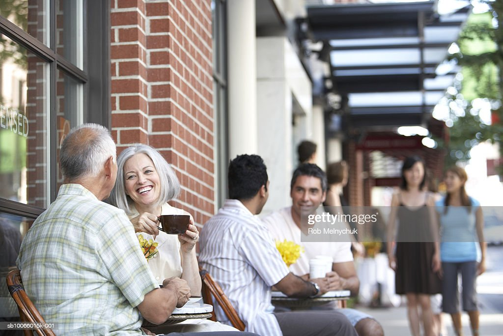 Couples sitting outside of coffee shop enjoying each other's company : Stock Photo