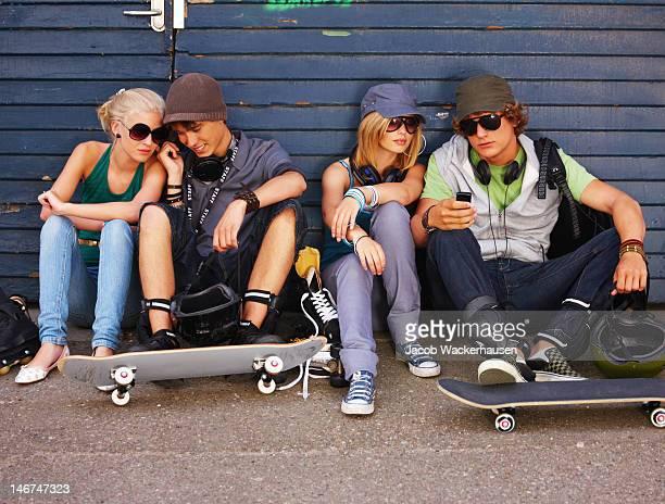Paare sitzen zusammen auf Straße und Blick auf Handy