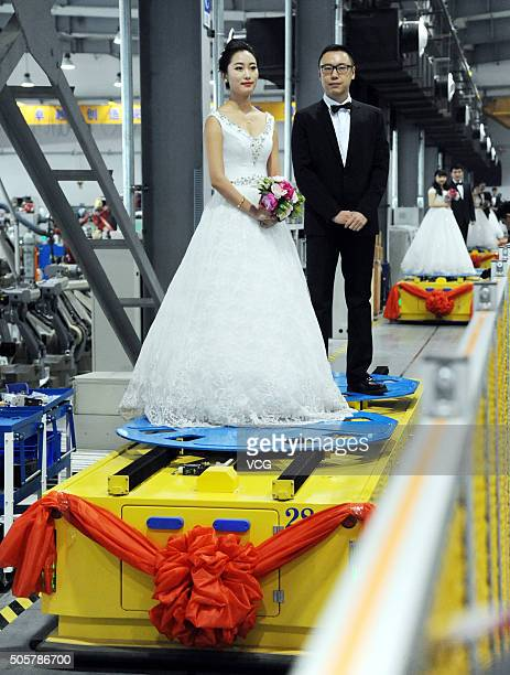 Couples stand on the robot moving forward during a group wedding ceremony at a robot factory on January 20 2016 in Shenyang Liaoning Province of...