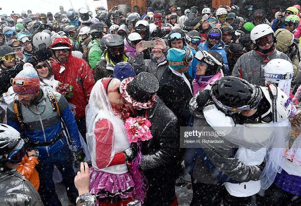 Couples Terri Looft, in red and white, and her husband Scott Wilson, in top hat, and Keith Engelman and his wife Leslie, right, kiss during the 25th annual Mountaintop Matrimony Valentine's day wedding ceremony on February 14, 2016 at the Loveland Ski area near Georgetown, Colorado. Both couples were renewing their wedding vows. The ceremony was held at Ptarmigan Roost cabin at the top of Ptarmigan lift. Approximately 100 couples got married or renewed their vows with minister Harry Heilmann, of the Universal Life Church, overseeing the ceremony.