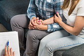 Couples therapy or marriage counseling. Man and woman holding hands on couch during a psychotherapy session.