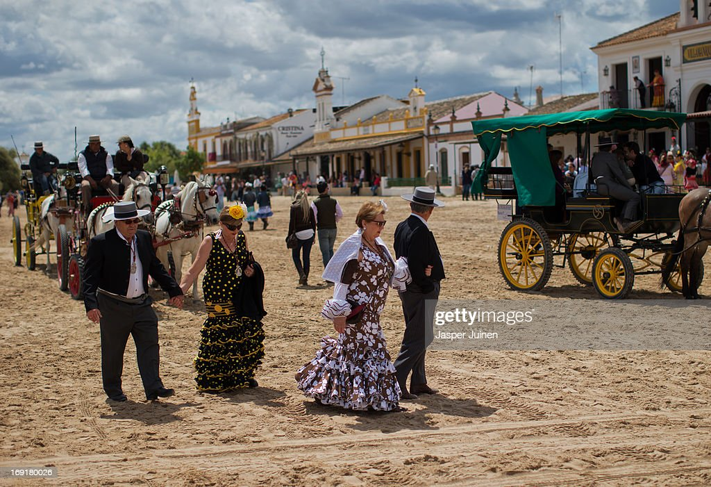 Couples walk the street on May 19, 2013 in El Rocio, Spain. The Romeria del Rocio procession brings together roughly a million pilgrims each year making their way for as long as seven days from throughout Andalusia by foot, on horsebacks and horse drawn carriages, to the doors of the Hermitage of El Rocio. On Sunday night, after reciting the Holy Rosary at candlelight, and the passing of all the simpecados in front of the chapel, with the one from the brotherhood of Matriz de Almonte as the last one, el salto de la reja begins, the jumping of the fence surrounding the Hermitage after which the Virgin of El Rocio is carried out onto the sandy streets of the small town for the 'Blanca Paloma' procession. Then, the long camino home begins. Dating back from 1653, it was in 1758, when the Virgin of Las Rocinas became known as the Virgin of El Rocio, that the pilgrimage started to take place in the weekend of the Sunday of Pentecost, 50 days after Easter Sunday.