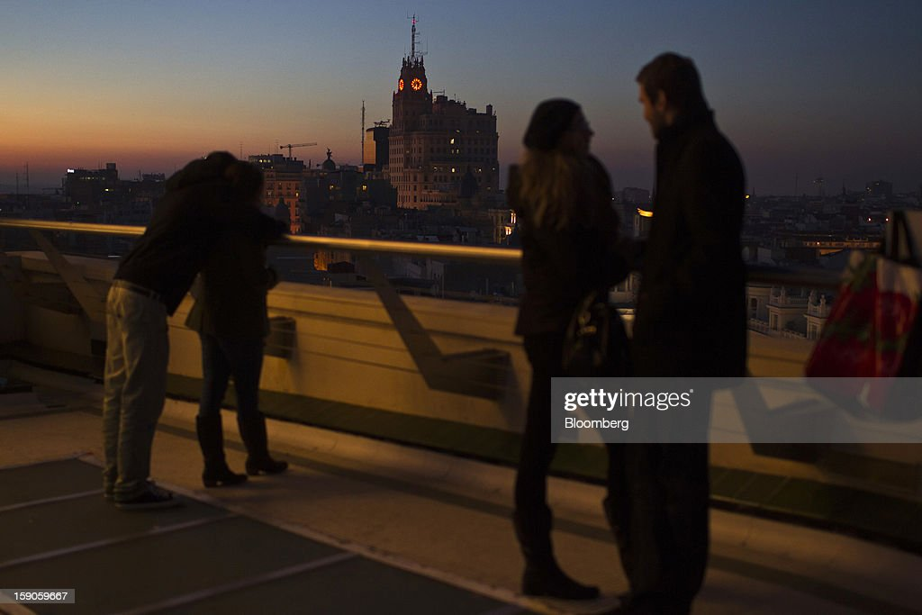 Couples watch the evening sun set over the city skyline in Madrid, Spain, on Saturday, Jan. 5, 2013. In December, the Spanish parliament passed an energy law that imposed a 7 percent tax on electricity generation from Jan. 1 to plug the deficit. Photographer: Angel Navarrete/Bloomberg via Getty Images