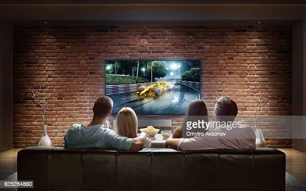 Couples watching car race game at home