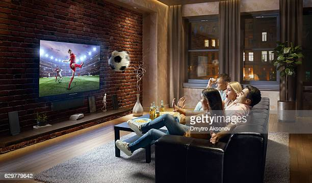 Couples watching very realistic Soccer game on TV