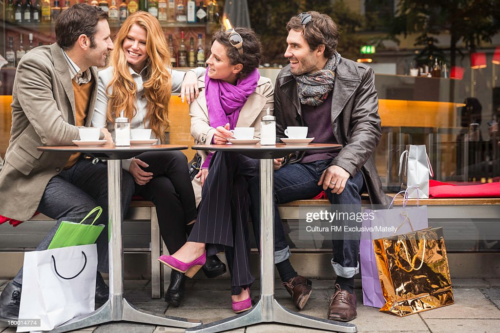 Couples with shopping bags at cafe : Stock Photo