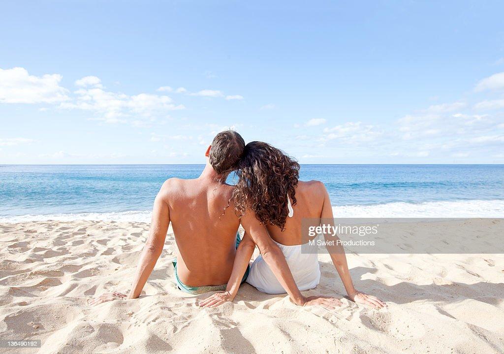 Couplesiting in beach in sunlight : Stock Photo