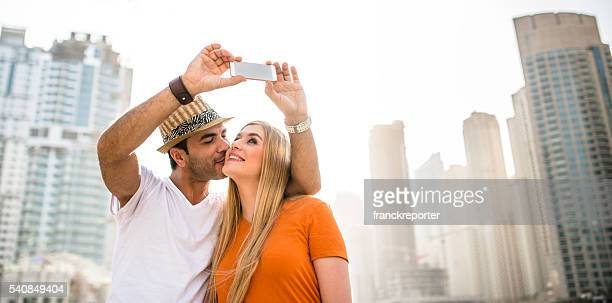 coupletake a selfie against the skyline of dubai marina