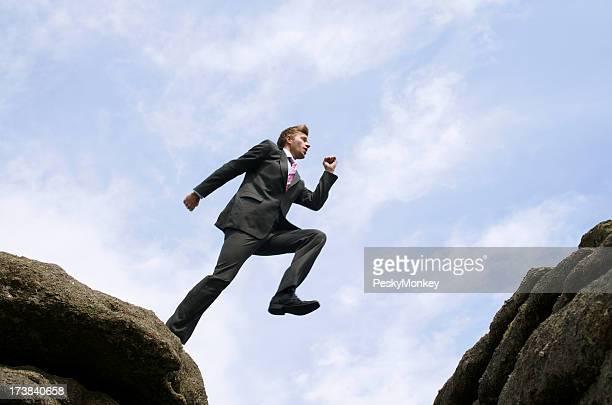 Courageux Homme d'affaires sautant de rocher du gouffre