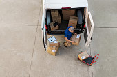 Delivery man holding cardboard box and unloading parcel for delivery. Top view of courier unloading parcels from van. High angle view of man removing packages for the delivery.