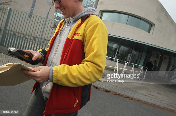A courier of international delivery service DHL departs after making a delivery at the Chancellery on November 3 2010 in Berlin Germany The day...