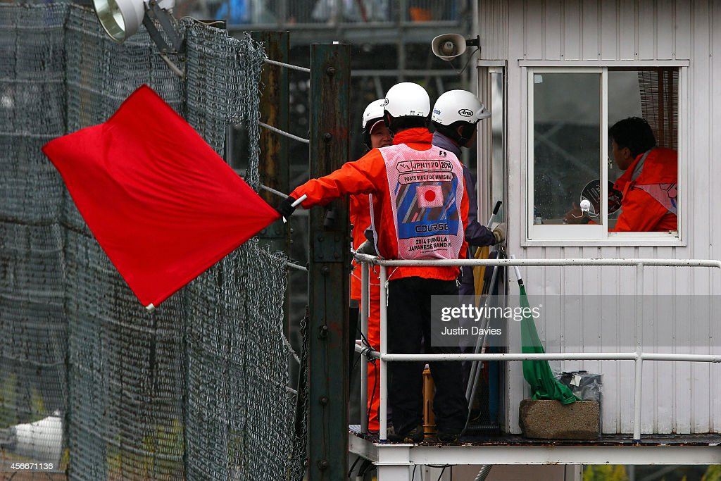 A course marshall waves a red flag during the Japanese Formula One Grand Prix at Suzuka Circuit on October 5 2014 in Suzuka Japan