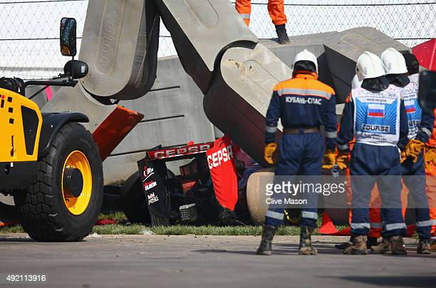 Course marshalls remove barriers from the top of Carlos Sainz of Spain and Scuderia Toro Rosso's damaged car after he crashed during final practice...