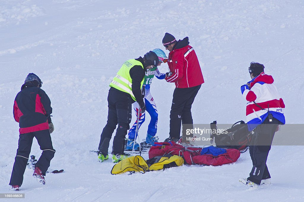 A course worker and first aid team assist Marie Marchand-Arvier of France after she crashed on the Kandahar course while competing in the Audi FIS Alpine Ski World Cup downhill race on January 12, 2013 in St Anton, Austria.