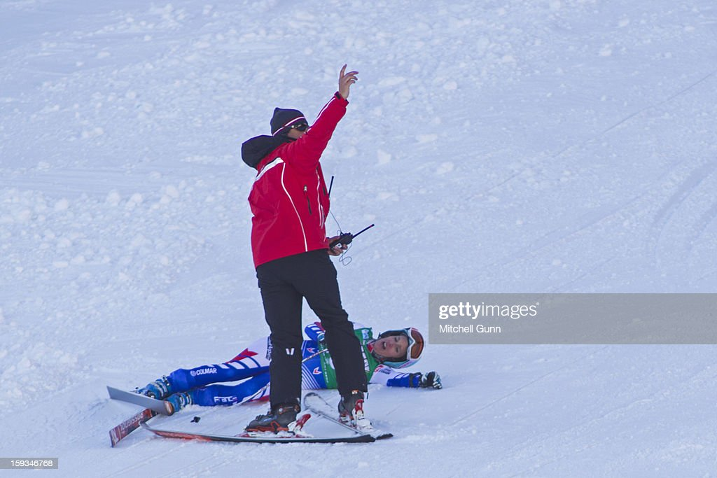 A course worker calls for a first aid team to assist Marie Marchand-Arvier of France after she crashed on the Kandahar course while competing in the Audi FIS Alpine Ski World Cup downhill race on January 12, 2013 in St Anton, Austria.