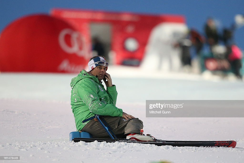 A course worker sits on the snow while talking on a mobile phone before the slalom section of the Alpine FIS Ski World Championships Super Combined race on February 11, 2013 in Schladming, Austria,
