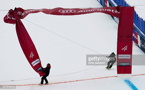 Course workers worker remove the finish line banner from the course after cancellation of the FIS World Cup Alpine Men's Downhill December 3 2010 in...