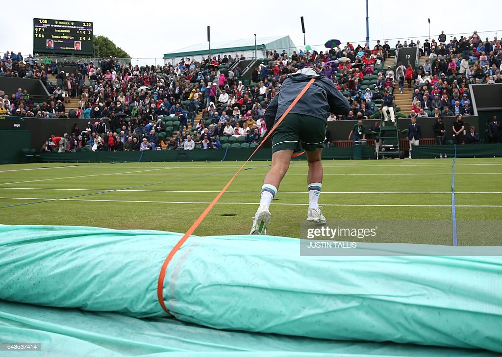 Court attendants pull the rain covers on court 2 as rain stops play during the third day of the 2016 Wimbledon Championships at The All England Lawn Tennis Club in Wimbledon, southwest London, on June 29, 2016. / AFP / JUSTIN