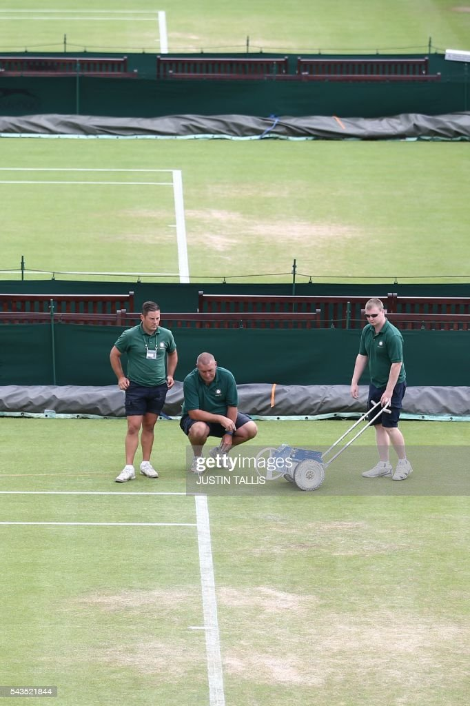 Court attendants re-paint the white lines on a court before the start of the third day of the 2016 Wimbledon Championships at The All England Lawn Tennis Club in Wimbledon, southwest London, on June 29, 2016. / AFP / JUSTIN