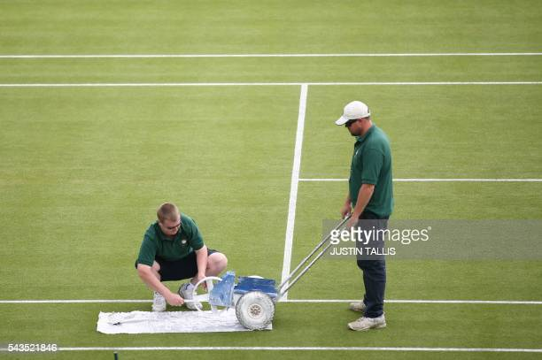 Court attendants repaint the white lines on a court before the start of the third day of the 2016 Wimbledon Championships at The All England Lawn...