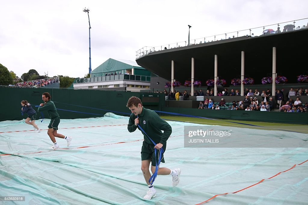 Court attendants uncover on outer court on the rain delayed third day of the 2016 Wimbledon Championships at The All England Lawn Tennis Club in Wimbledon, southwest London, on June 29, 2016. / AFP / JUSTIN