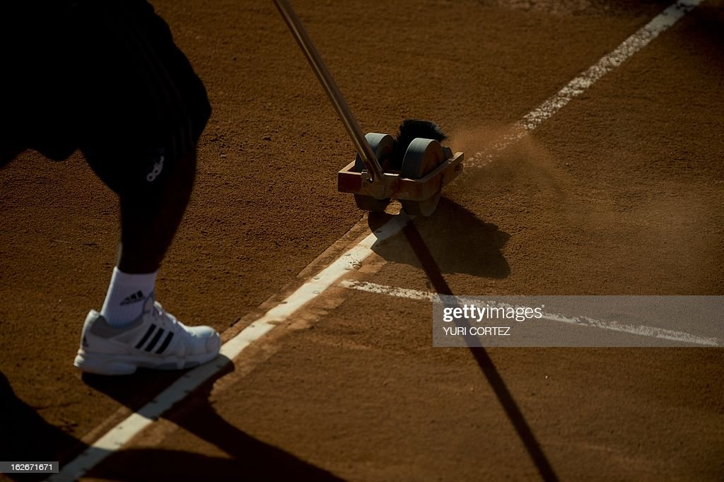 A court staff cleans the line during the game between Pablo Andujar of Spain and Dusan Lajovic of Serbia during Mexican Tennis Open on February 25, 2013 in Acapulco, Guerrero state, Mexico. AFP PHOTO/ Yuri CORTEZ