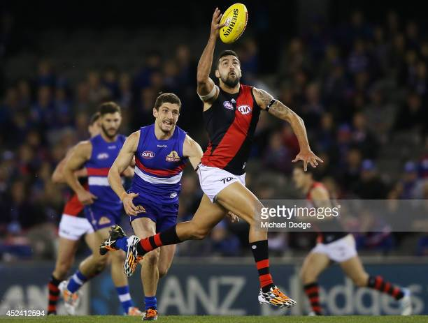 Courtenay Dempsey of the Bombers gathers the ball from Tom Liberatore of the Bulldogs during the round 18 AFL match between the Western Bulldogs and...