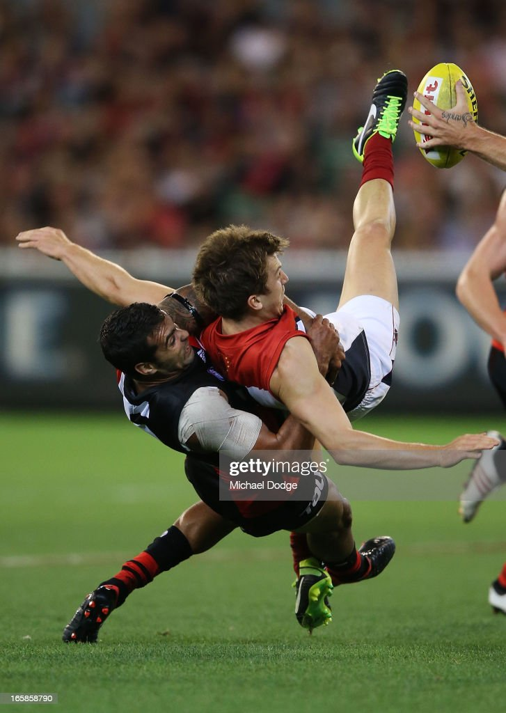 Courtenay Dempsey of the Bombers tackles Jack Trengove of the Demons during the round two AFL match between the Essendon Bombers and the Melbourne Demons at Melbourne Cricket Ground on April 6, 2013 in Melbourne, Australia.