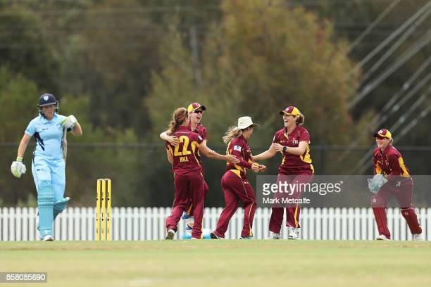 Courtney Hill of Queensland celebrates with team mates after taking the wicket of Alyssa Healy of NSW during the WNCL match between New South Wales...