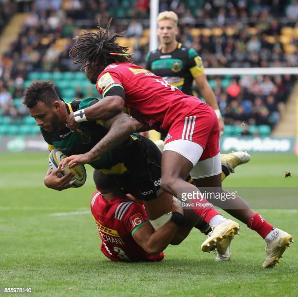 Courtney Lawes of Northampton is tackled by Joe Marchant and Marland Yarde during the Aviva Premiership match between Northampton Saints and...