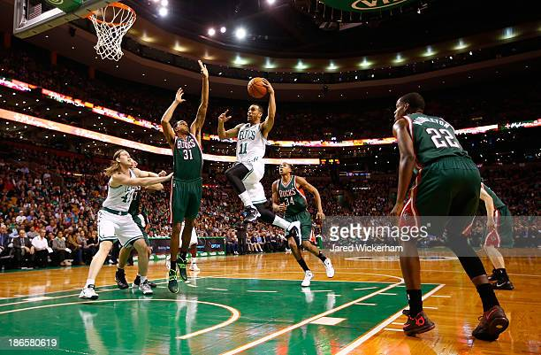 Courtney Lee of the Boston Celtics drives to the basket in front of John Henson of the Milwaukee Bucks in the first quarter during the home opener at...